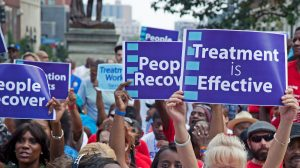 """protest with sign that reads """"treatment is effective"""""""
